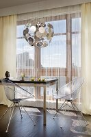 Clear, plexiglas shell chairs at modern dining table and Dandelion classic pendant lamp in front of glass wall with thread curtain