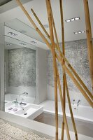 Artistic bathroom with reflective mirrored surfaces; elephant-skin structure above bathtub and bamboo canes in foreground