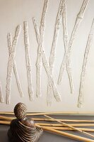 Bamboo canes, Buddha figurine and bamboo relief on wall