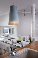 Pendant lamp with elegant fringed lampshade above dining table; sink unit with retro tap fittings in foreground