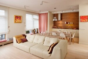 Wood and pink accents in cream living-dining room with large sofa and classic chairs in background