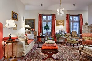 Interior filled with antique seating and side tables with mixture of patterns on Oriental rugs and traditional upholstery fabrics
