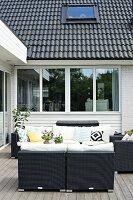 Dark rattan outdoor furniture on wooden terrace