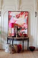 Collection of vases and abstract artwork on vintage console table