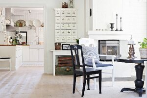 Round black table and chairs in front of fireplace next to wide, open doorway with view into kitchen