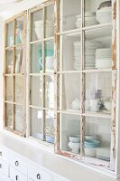 Crocker in glass-fronted dresser with peeling white paint