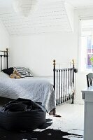Vintage metal bed with grey bedspread in attic room with white, wood-clad sloping ceiling