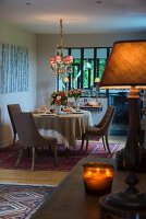 Set dining table and upholstered chairs below chandelier with small lampshades; tealight holders and table lamp providing warm glow in foreground