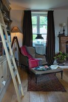 Living room with wooden ladder next to bookcase, standard lamp, armchair below window and floor-length curtains