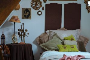 Vintage-style candelabra and table lamp on side table next to bed with scatter cushions arranged against dark brown bed headboards