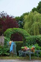 Vintage wheelbarrow decorated with harvested vegetables in front of trellis arch over garden gate and hedge