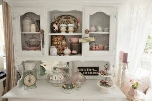 Antique kitchen scales and cake stands on white-painter dresser with crockery and knick-knacks in top section with chicken-wire door panels