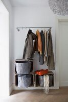 Coats hanging from open coat rack above felt baskets in wooden crates