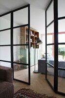 Open door in steel and glass wall with view of cabinet, standard lamp and sofa in living area