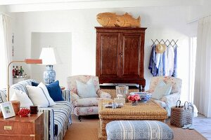Romantic living room with various upholstered seating and antique wooden cupboard