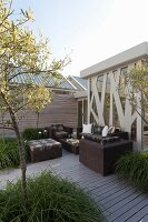 Trees in large planters and modern, dark wicker outdoor furniture on wooden terrace