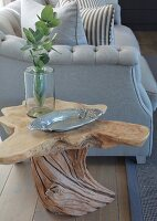 Organically shaped wooden side table next to elegant sofa