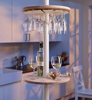 Round minibar with wine glass rack on telescopic pole in kitchen