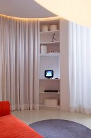 Tiny TV on curved shelves between white partition curtains and round, pale grey rug in front of orange sofa in living area