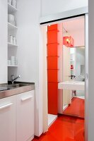 Kitchenette with sink and shelving in niche next to open sliding door with view of sink on floor-to-ceiling mirror and continuous orange floor