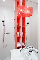 Sink mounted on mirrored panel, orange shelves of toiletries and shower head in shower area of studio apartment