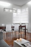 Corner of stylish interior with dining area, long wooden table and modern chairs on exotic wood floor; white closed roller blinds on corner window