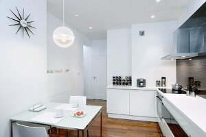 Dining table with breakfast place settings in open-plan, white, modern kitchen