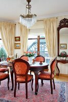 Antique wooden chairs and red and gold upholstery around dining table in grand dining area with pale, draped curtains on French windows