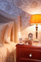 Bedside lamp with yellow lampshade on mahogany bedside cabinet; bed with headboard against wall with pale, silk floral wallpaper
