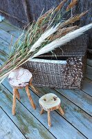 Rustic wooden stools next to wicker trunk and bunch of pampas grass on wooden deck