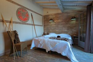 Double bed with white bedspread against wood-clad wall, wicker chair and pampas grasses to one side in rustic bedroom