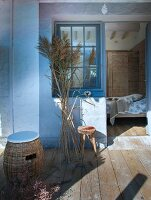 Wicker stool with seat cushions and bunch of pampas grass on wooden terrace with view into bedroom