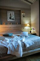 White dressing gown on bed against wood-clad wall with niche and table lamp