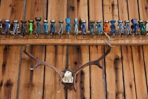 Row of brightly-painted poppy seed grinders on wooden beam above hunting trophy on wall