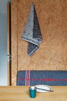 Printed tea towel pinned to wall made from plain OSB board above grey backrest of bench and place setting on dining table
