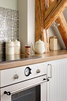 Kitchen counter with modern, retro-style cooker and embossed tiled splashback integrated into rustic roof-beam structure
