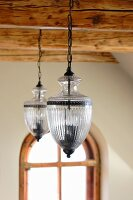 Pendant lamps suspended between wooden roof beams
