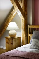 Ceramic lamp on bedside cabinet and wooden bed below sloping ceiling with rustic wooden beams