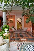 Plants in conservatory opening into lounge with chequered tiled floor and row of columns