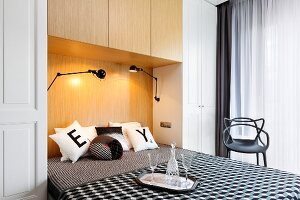 Double bed in niche of fitted wardrobes, black and white patterned bed linen and scatter cushions, carafe and glasses on tray