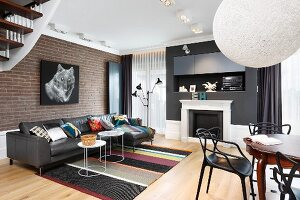 Black furniture, graphic patterns and picture of animal on brick wall in modern living room