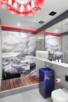 Designer bathroom with blue pedestal sink in front of glazed shower area with black and white photo mural