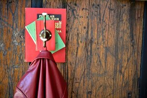 Coat peg hand-crafted from books and hook on rustic wooden wall
