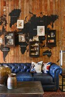 Vintage, blue leather couch against wooden wall with painted world map, small wall-mounted cabinets and pictures; rustic containers on coffee table in foreground