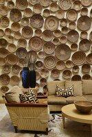Sammlung von handgefertigten Holzschüsseln an Wand, davor Sofagarnitur aus Geflecht mit farblich abgestimmten Polstern und Kissen mit grafischem Muster