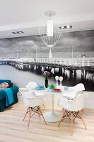 Tulip table, Eames Plastic Armchairs and blue sofa in front of black and white mural wallpaper depicting long wooden pier in the ocean