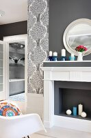 Elegant, grey and white faux fireplace and chimney breast and colourful ethnic scatter cushion on chair; view into bathroom in background