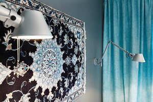 Silk rug on bedroom wall flanked by Tolomeo lamps with pastel blue curtain in background
