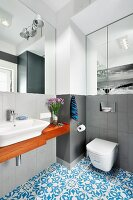 Grey walls in monochrome bathroom combined with wooden washstand and Oriental blue tiled floor
