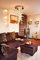 Pendant lamp with glass bubbles above dark brown corner sofa with matching ottoman; elegant interior with ethnic elements